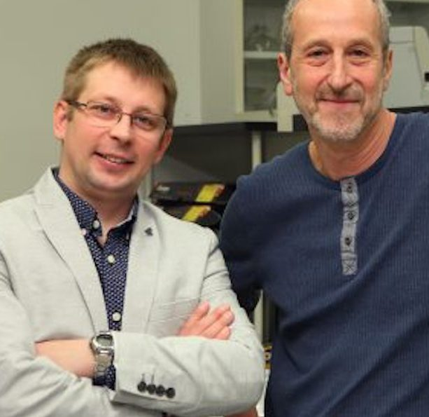 two men in posing in front of some lab shelves